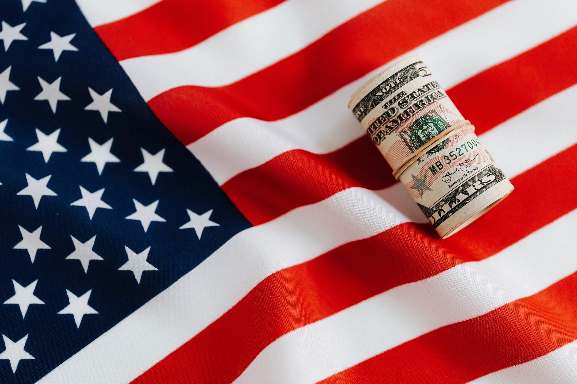 american flag with rolled dollar bills
